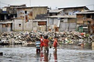 Beberapa anak melintas di dekat bangunan liar yang terendam air.