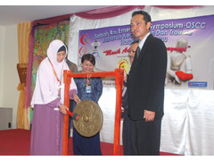 Dr. Zuraidah memalu gong tiga kali sebagai tanda rasminya simposium