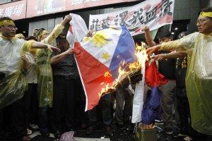 Para pengunjuk rasa dan anggota parlemen membakar bendera Filipina