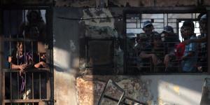 Narapidana berada di balik jeruji tahanan dengan bangunan yang terbakar di Lembaga Pemasyarakatan (Lapas) Klas I Tanjung Gusta, Medan,