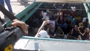 Ratusan imigran gelap tidur dan duduk santai saat berada di dalam kapal penumpang setelah tertangkap di Perarian Selat Badung , Bali,
