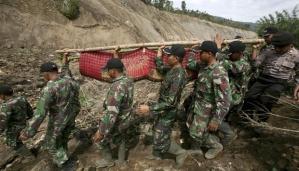 Sejumlah anggota TNI AD mengangkat mayat korban gempa bumi yang tertimbun oleh tanah lonsor di Serempah, provinsi Aceh