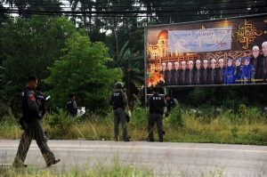 Explosives experts check the area around a roadside sign announcing Ramadan
