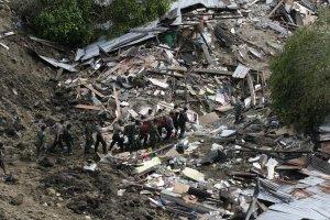 Personel TNI dan polisi mengevakuasi jenazah Lilis (11), korban gempa yang tertimbun longsor