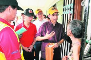 Profesor Faishal bersama Encik Ang (kemeja-T merah) dan Pengarah Besar, Kesihatan Awam NEA, Encik Derek Ho (kemeja-T putih), sama-sama mengagihkan ubat penghalang nyamuk