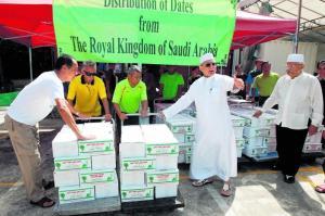 Habib Hassan Al-Attas (berjubah putih) menyaksikan pengagihkan 45,000 kilogram, atau 45 tan, kurma 'Barni' yang dihadiahkan kerajaan Arab Saudi