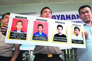 MASIH DIBURU: Jurucakap polis Sumatera Utara, Encik Raden Heru Prakoso, menunjukkan gambar empat pengganas,