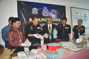 NOOR Rashid Ibrahim (tengah) bersama Mohd. Mokhtar Mohd. Sharif (dua dari kiri) menunjukkan wang, dadah dan pistol yang dirampas