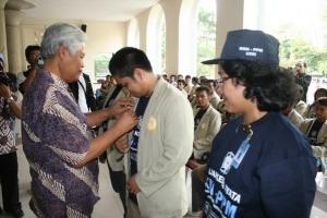 Rektor UGM, Soedjarwadi menyematkan pin kepada salah satu mahasiswa KKN.