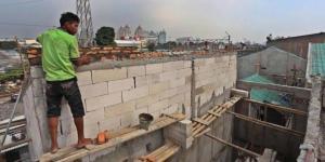 Pekerja menyelesaikan pembangunan Kampung Deret di Jalan Tanah Tinggi
