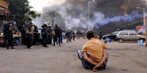 Seorang penunjuk perasaan, dalam keadaan terikat duduk menyaksikan aparat keamanan Mesir membubarkan para pendukung Muhammad Mursi