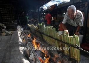 Pak Ali sentiasa memeriksa lemang yang dibakar agar tidak hangus.