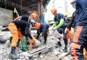 Beberapa anggota penyelamat, mengangkat mayat lelaki yang maut ditimbus runtuhan akibat gempa bumi.