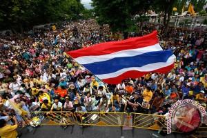 Penyokong Perikatan Rakyat untuk Demokrasi (PAD) yang berkaus kuning, mengibarkan bendera Thailand saat aksi unjuk rasa di luar bangunan Parlimen di Bangkok
