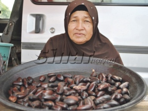 Fatimah menunjukkan buah perah dijualnya di Pasar Bukit Payung