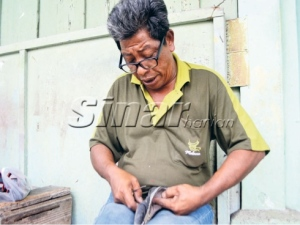 Abdul Aziz membaiki kasut pelanggan.