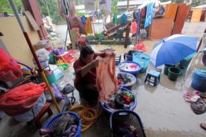 Norzawati Ibrahim, 41, membasuh pakaian ketika membersihkan rumahnya yang ditenggelami air akibat banjir