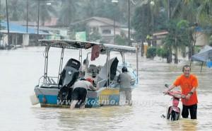 SEORANG mangsa banjir menolak motosikalnya yang rosak akibat banjir