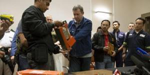 Seorang penyidik Malaysia (kiri) menerima sebuah kotak hitam saat kotak itu diserahkan oleh seorang pejabat Republik Rakyat Donetsk di kota Donetsk, Selasa (22/7/2014).