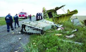 BLOWN TO PIECES: Ukrainian rescuers walk past debris at the crash site of the plane. (AP)
