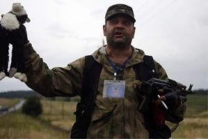 A pro-Russian separatist holds up a stuffed toy found at the crash site. – Reuters