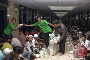 Petugas membagikan zakat berupa beras saat buka bersama di Masjid Istiqlal, Jakarta Pusat, Minggu (27/7). (ANTARA FOTO/Vitalis Yogi Trisna)