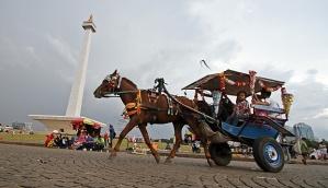 Pengunjung naik delman melintas di depan Monas ketika libur Natal di Monas, Jakarta,