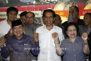 JOKOWI (tengah) memegang tangan Megawati (kanan) dan Jusuf sebelum pengumuman rasmi keputusan pilihan raya Presiden diumumkan di Jakarta semalam.