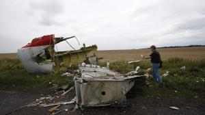 An Organisation for Security and Cooperation in Europe (OSCE) monitor takes a photograph at the crash site of Malaysia Airlines flight MH17, near the settlement of Grabovo in the Donetsk region on July 18, 2014.   -- PHOTO: REUTERS
