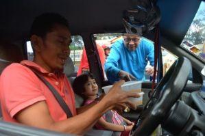 Ismail (baju biru) mengagihkan bubur lambuk pada Program Keselamatan Jalan Raya Bersama Ketua Pengarah JPJ dan Program Pengagihan Bubur Lambuk Kepada Pengguna Jalan Raya di sini, Rabu.