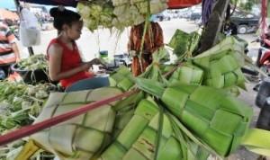 Pedagang merangkai janur kelapa menjadi ketupat