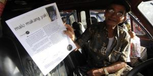 Salah satu penumpang jurusan Kakas, Minahasa sedang memperlihatkan LEAFLET berisi Kampanye Malo Makang Yaki yang disebarkan FORUM F/21.