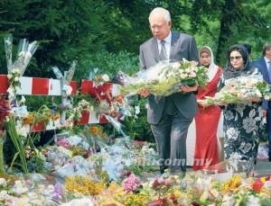 NAJIB Tun Razak dan Rosmah Mansor meletakkan sejambak bunga di luar berek tentera di mana pakar-pakar forensik bertungkus lumus untuk mengenal pasti mayat mangsa nahas pesawat MH17  - AGENSI
