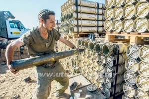 Seorang tentera Israel menyusun stok peluru meriam di lokasi operasi ketenteraan di sempadan Genting Gaza, semalam. - AFP