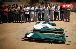 People pray next to the bodies of Palestinians from the al-Silk family during their funeral in Gaza City