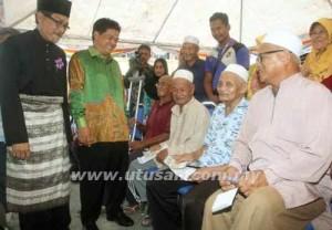 Abdul Razak Mohd. Zailan (kiri) beramah mesra dengan para penerima sumbangan di Kuala Terengganu, kelmarin.