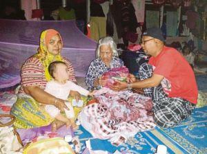 RAHIMI Yaacob (kanan) menghulurkan bantuan makanan kepada Minah (tengah) sambil diperhatikan anak bongsunya, Maznah Shafie di Kampung Pasir Tumboh.