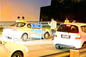 PETUGAS Jabatan Siasatan dan Kawalan Lalu Lintas (JSKLL), Pasukan Polis Diraja Brunei (PDB) Daerah Brunei dan Muara  membuat pemeriksaan dalam sekatan jalan raya. (Foto : Muhammad Asri Haji Awang Abas)