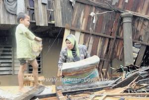 SITI KHADIJAH (kanan) mencari lebihan kayu-kayu sisa runtuhan rumahnya untuk digunakan membina penempatan sementara di Kampung Manik Urai Lama, Kuala Krai baru-baru ini.
