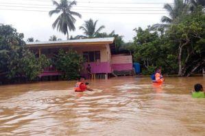Anggota Bomba dan Penyelamat memindahkan mangsa banjir setelah Kampung Rugading mula dinaiki air di Tawau, Jumaat. Foto BERNAMA